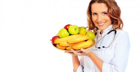dietetyk zajmujący sie rozpisywaniem diet, trzyma tace owoców